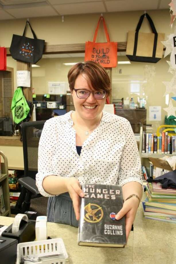 Tirzah Price, Big Rapids Community Library clerk, hands out a banned book and a button for earning five points in the Banned Books Week Challenge. (Pioneer photo/Candy Allan)