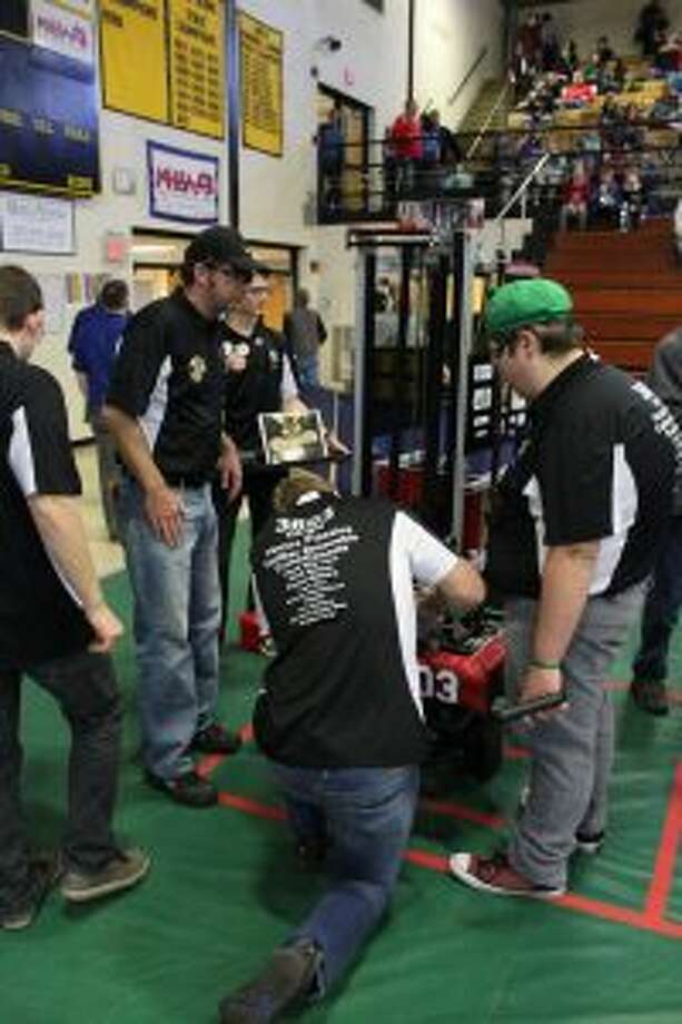 The Reed City Cyber Coyotes work on their robot during their first competition of the season. The team will be competing in the state championship this weekend at Saginaw Valley State University. (Pioneer file photo)
