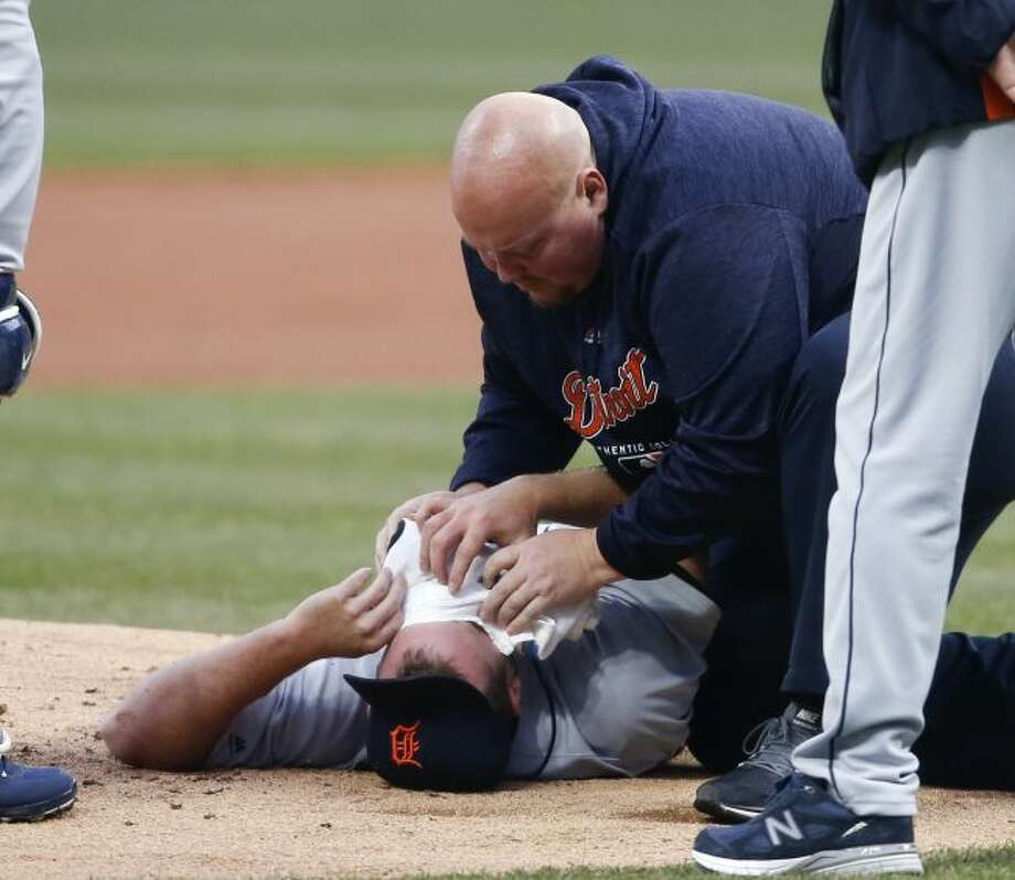 Detroit Tigers starting pitcher Jordan Zimmermann is tended to by head athletic trainer Doug Teter after getting hit by a ball off the bat of Cleveland Indians' Jason Kipnis during the first inning in a baseball game Wednesday, April 11, 2018, in Cleveland. (AP Photo/Ron Schwane)
