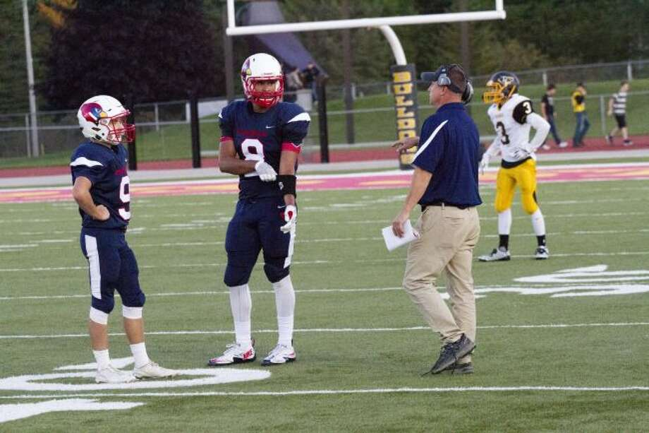 Big Rapids quarterback Aaron Repke (9) and tight end Braeden Childress (8) talk with head coach Mike Selzer during a recent game. (PIoneer file photo)