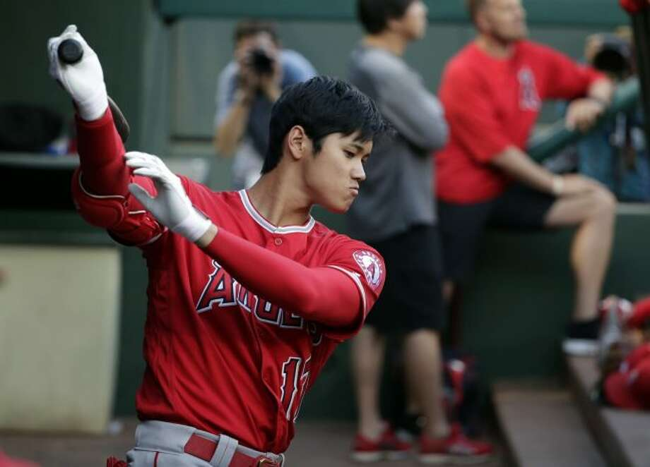 In this April 11, 2018, file photo, Los Angeles Angels' Shohei Ohtani takes a practice swing in the dugout in the first inning of a baseball game against the Texas Rangers in Arlington, Texas. Ohtani eagerly bounces into the cage when it's his turn in batting practice _ and then puts on an impressive show. The rookie two-way sensation is always ready to go, whether hitting or pitching for the Angels. (AP Photo/Tony Gutierrez, File)