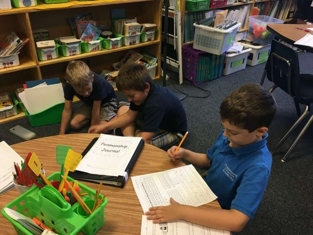 Students in Vicky Bowman's second- and fourth-grade split class work at small tables, the floor or in other areas of the room to complete their assignments in a Montessori-inspired program. (Courtesy photos)