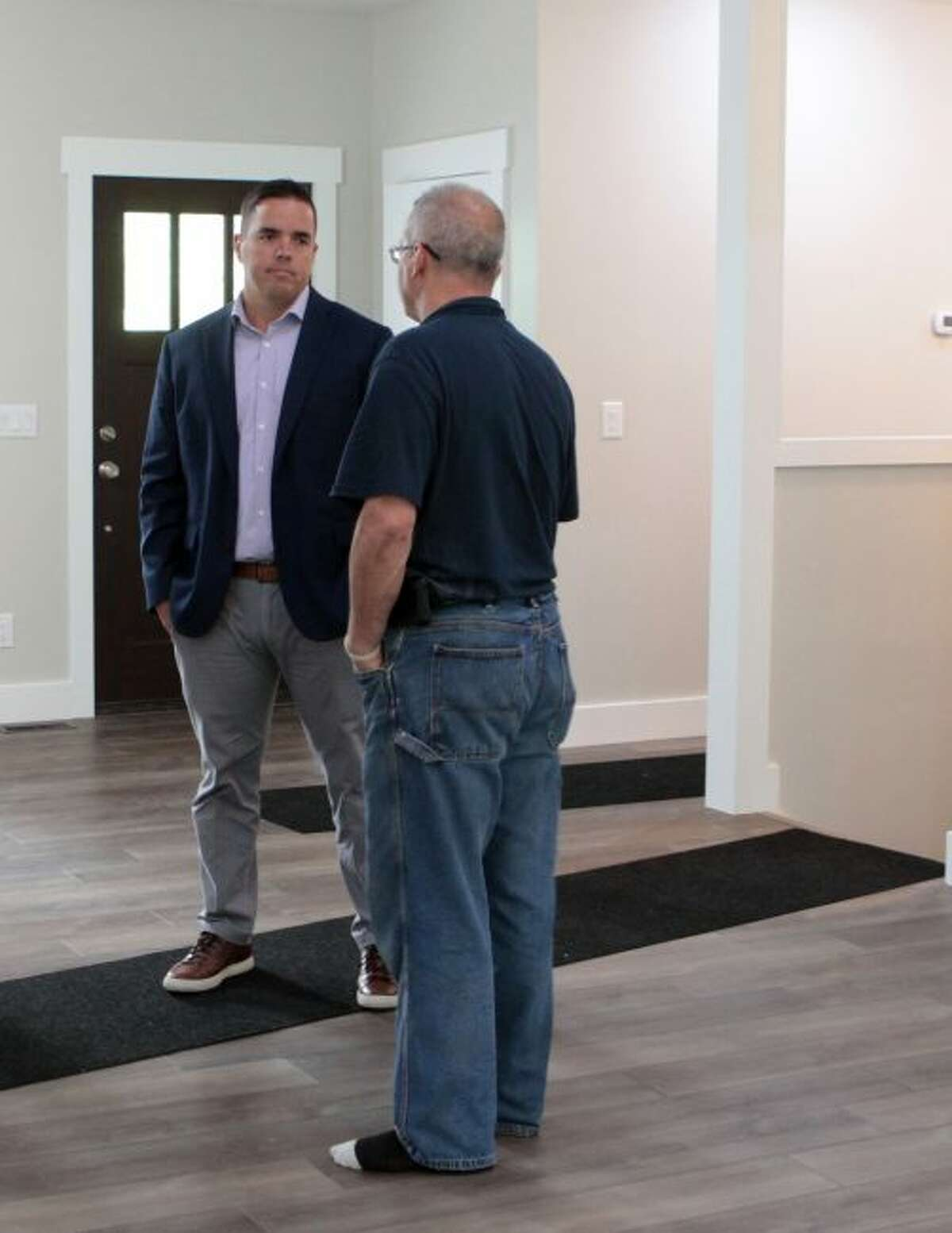 Construction trades teacher Doug Sickles (front) shows MOISD superintendent Steve Locke around the new home built by local students. (Pioneer photo/Taylor Fussman)