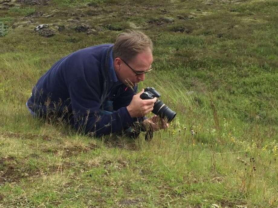 Ralph Crew, of Big Rapids, works on getting a good shot of a wildflower. Crew has developed a wildflower identification website indexing area blooming plants by date of flowering and color. (Courtesy photo)
