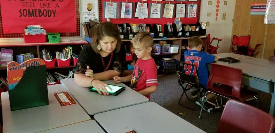 G.T. Norman Elementary teacher, Karah Hensel, works with second-grader Drake Dennis to turn on a program to listen to books. Hensel is in her first year of teaching in the Reed City Area Public Schools district. (Pioneer photo/Meghan Gunther-Haas)