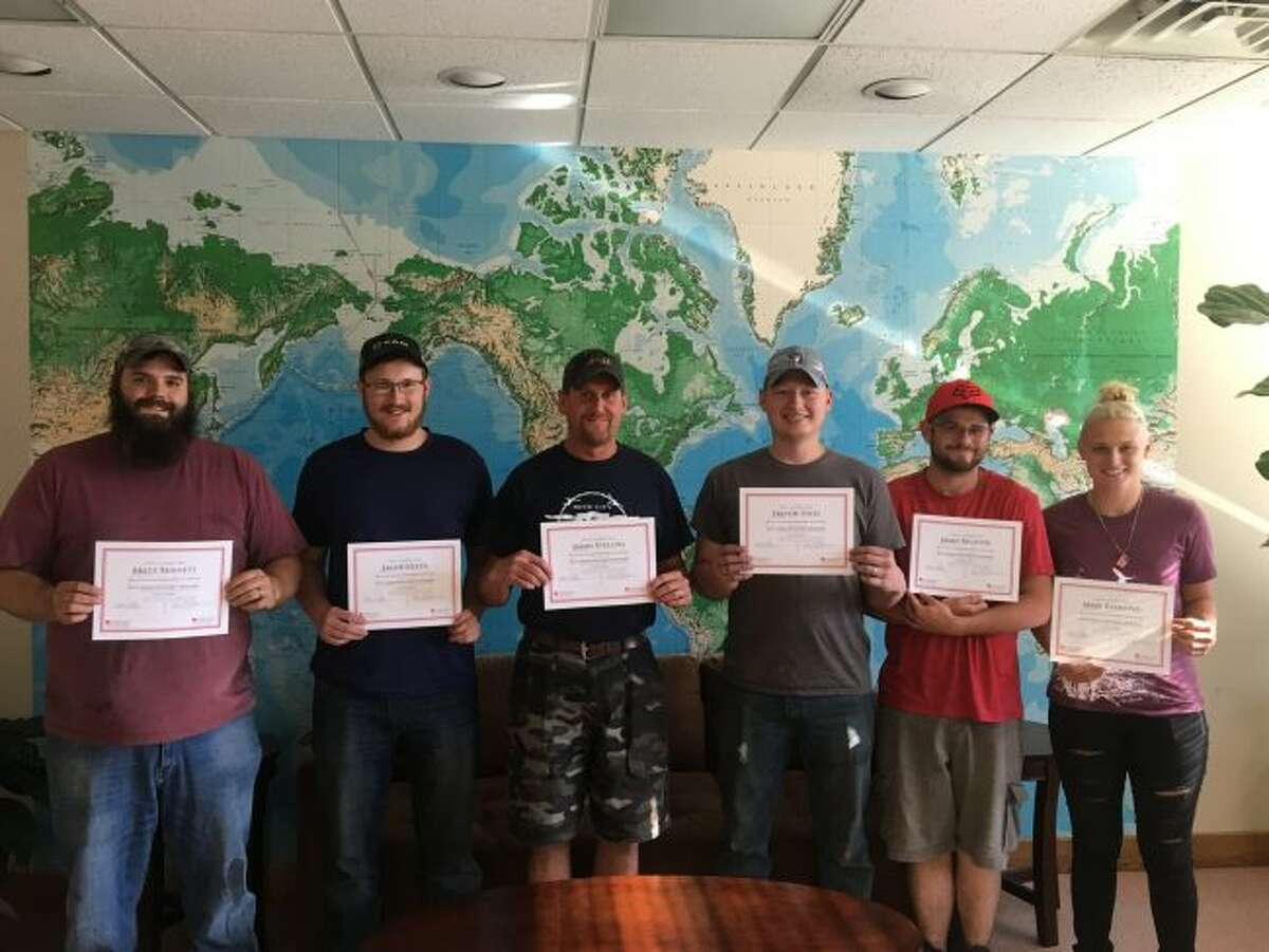 Reed City Group employees (from left) Brett Bennett, Jacob Green, Jason Stellini, Trevor Thiel, James Bechtol and Mary Raymond hold certificates they received after completing Ferris State University training in injection molding technology. (Courtesy photo)