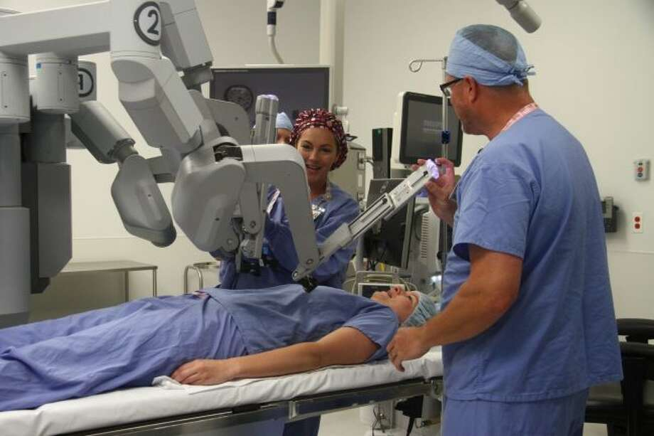 In July in an operating room at Spectrum Health Big Rapids Hospital, Beth Nicholson, certified surgical technologist, and Dr. Mark Haan, a general surgeon, demonstrate with the help of a volunteer where the da Vinci robot-assisted surgery system's arms would be placed during a hernia procedure. (Pioneer file photo)