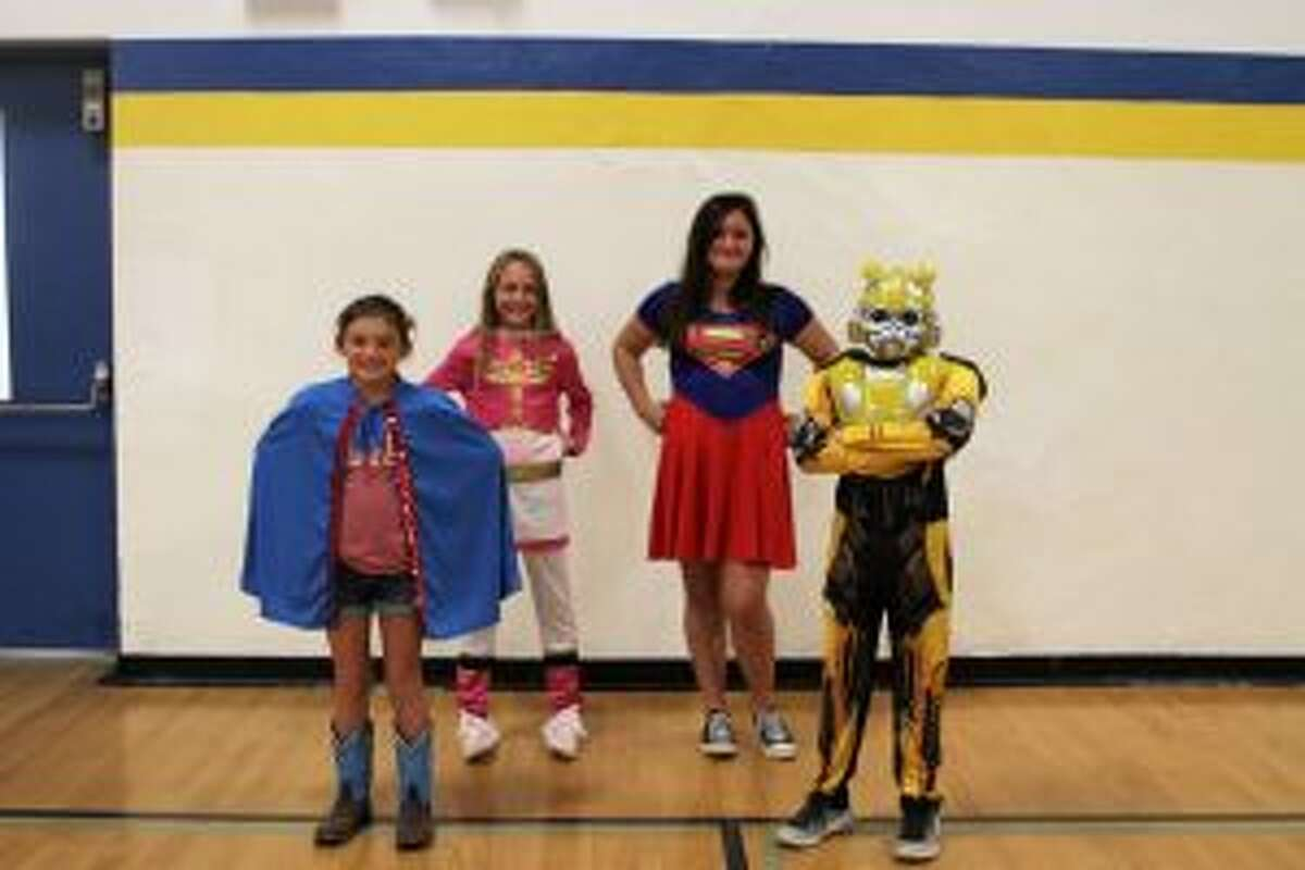 Evart Middle School students strike a heroic pose on Villain vs. Superhero Day on Tuesday. Homecoming week dress-up days will continue with Mutant Day in the middle school.