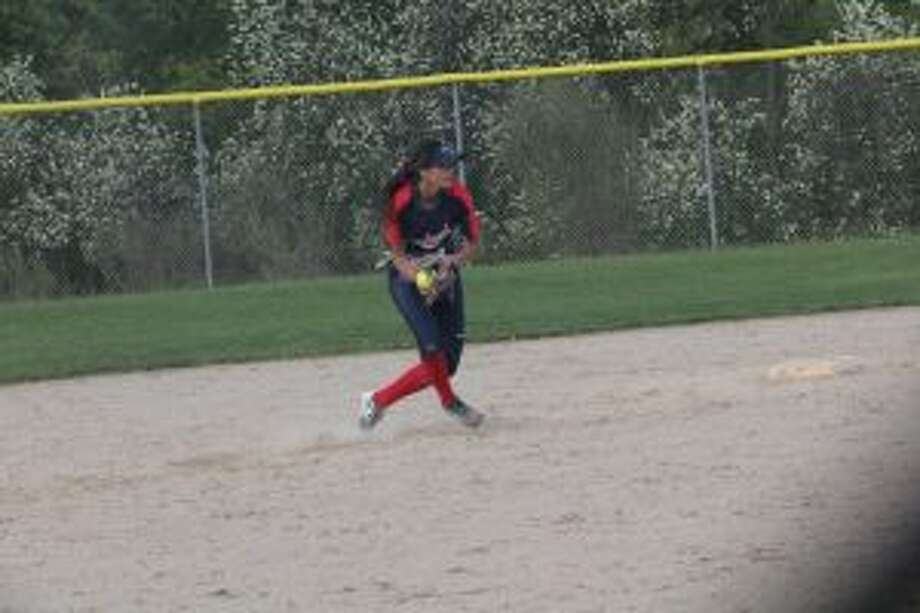 Big Rapids' Emma Daum makes the throw to first base.