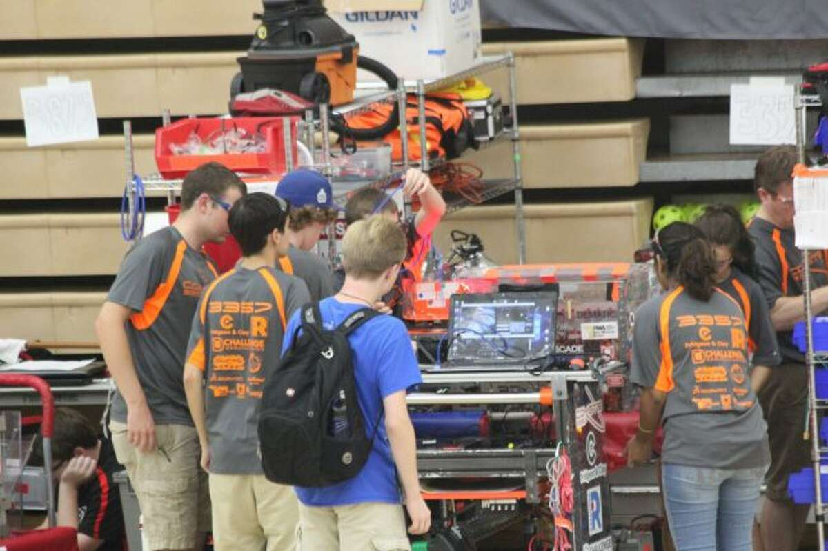 The Comets from Grand Rapids work on their robot in the pits during Saturday's inaugural FIRST Robotics Competition Roboday at Ferris State University's Wink Arena. Teams from Big Rapids High School and Crossroads Charter Academy hosted the event. (Pioneer photo/Brandon Fountain)