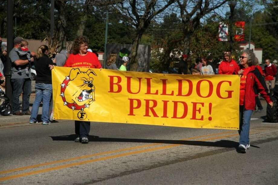 "Participants of the 2017 Ferris State University homecoming parade carry a ""Bulldog Pride"" toward the start of the procession down Michigan Avenue. This year's parade will begin at noon on Saturday, Sept. 29. (Pioneer file photos)"
