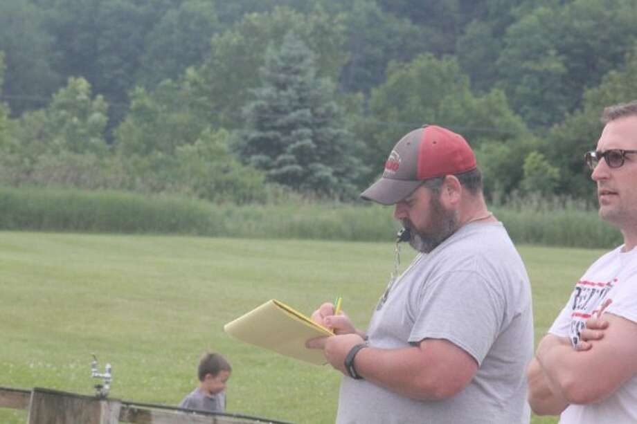 Reed City football coach Scott Shankel jots down some notes prior to a summer workout on Sunday. (Pioneer photo/John Raffel)