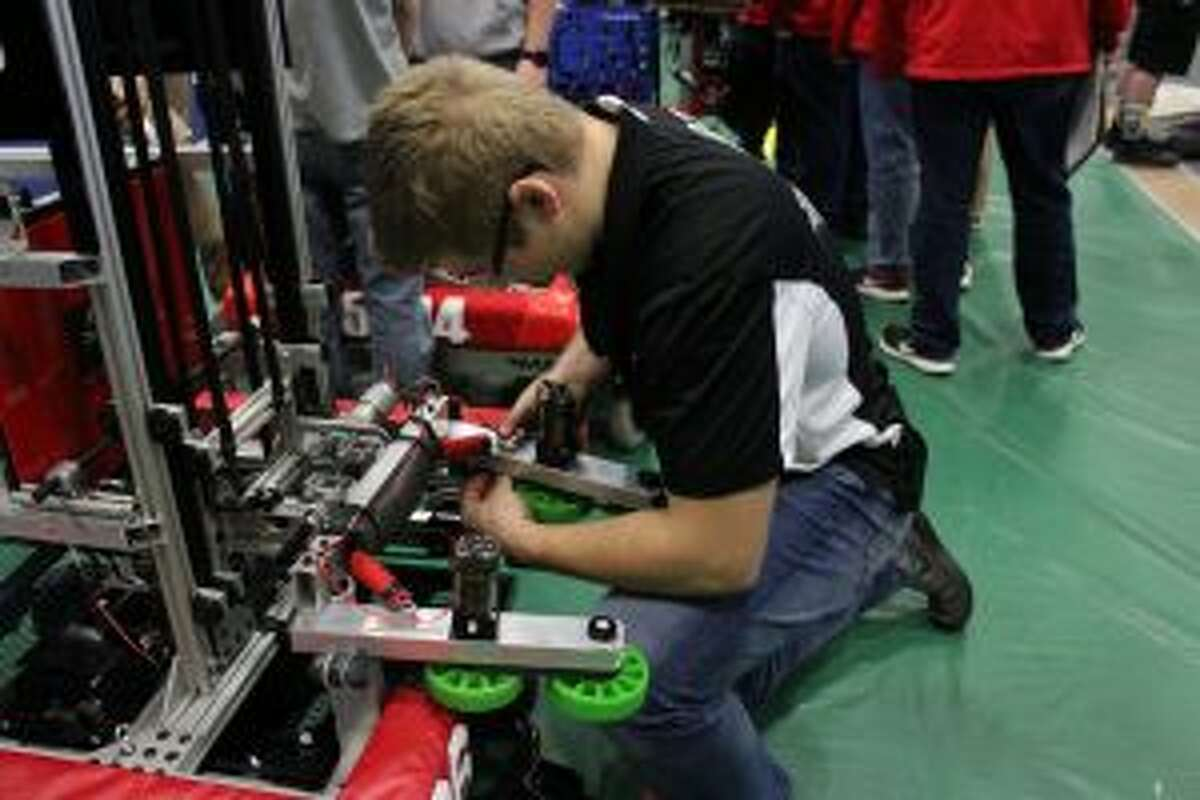 Reed City's Stephen Shewan puts the finishing touches on the team's robot before action during a district event this season. After competing in the state championships this weekend, the team is looking forward to applying what they have learned when the next season starts.