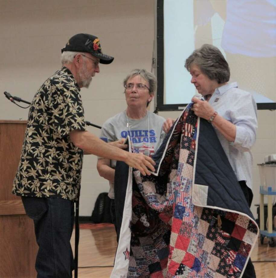 Vietnam War veteran Leon Motz (left) was surprised with a quilt from members of the Big Rapids chapter of the Quilts of Valor Wednesday afternoon during Senior Enrichment Day. (Pioneer photo/Taylor Fussman)