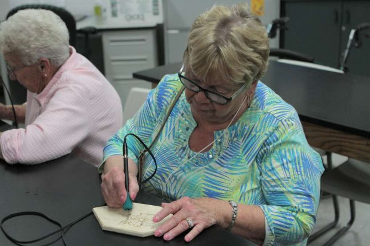 Kay Jones, a longtime attendee of Senior Enrichment Day, practices her wood burning skills during this year's event. (Pioneer photo/Taylor Fussman)