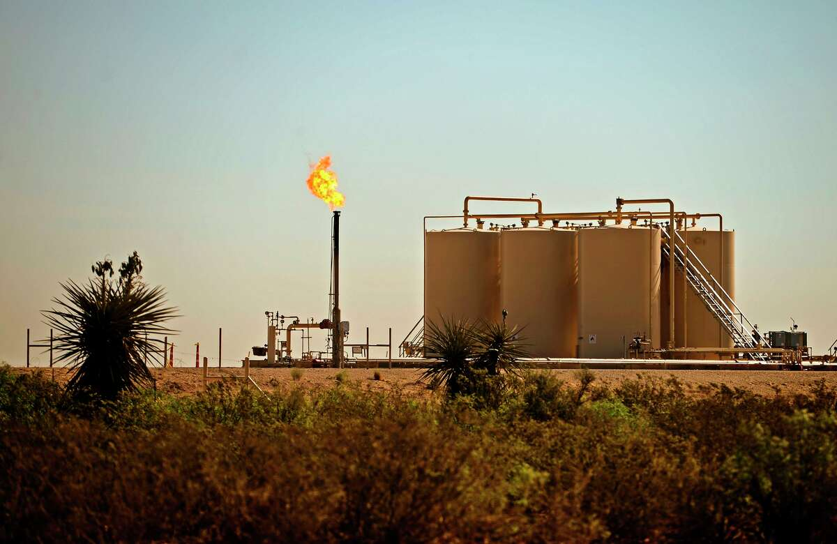 A natural gas flare is visible near storage tanks May 30, 2018, in Reeves County, Texas.