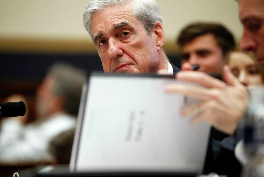 Former special counsel Robert Mueller, checks pages in the report as he testifies before the House Judiciary Committee hearing on his report on Russian election interference, on Capitol Hill, Wednesday, July 24, 2019 in Washington. (AP Photo/Alex Brandon) Photo: Alex Brandon / Associated Press / Copyright 2019 The Associated Press. All rights reserved.