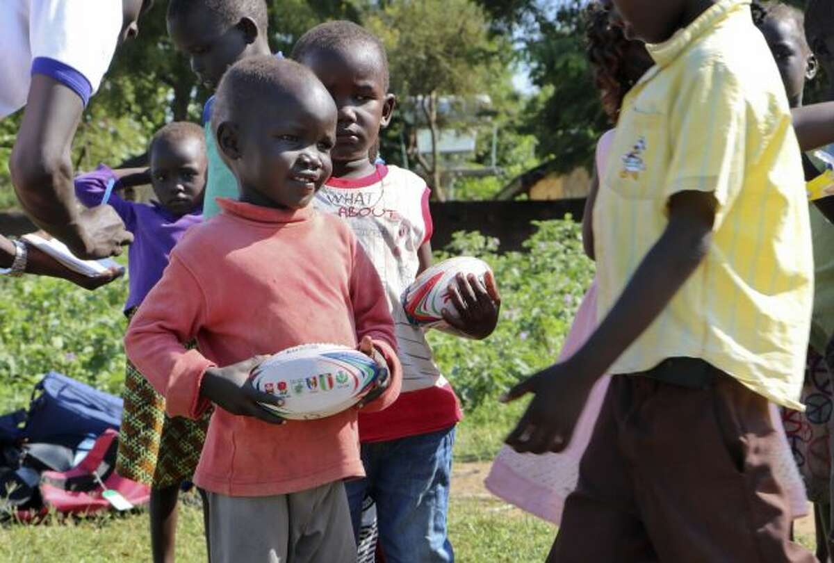 In this photo taken Saturday, Sept. 1, 2018, boys get ready to play rugby during the South Sudan Rugby Club's weekly practice in Juba, South Sudan. The country this year launched its first rugby league since independence, finding in the rough-and tumble sport a way to promote peace, with more than 200 children having signed up for practices run by volunteers, many of whom learned to play as refugees. (AP Photo/Sam Mednick)