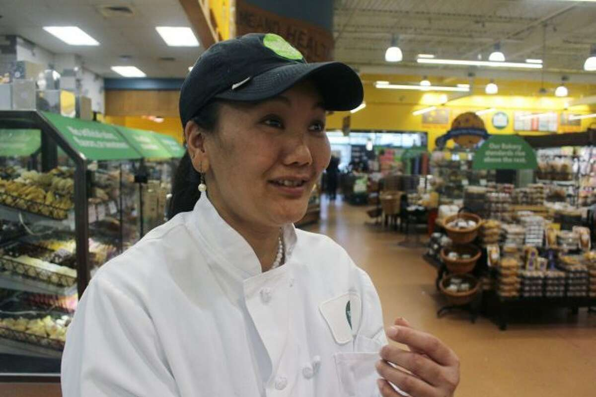 In this April 3, 2018, photo, mountain climber Lhakpa Sherpa prepares to start her shift as a dishwasher at the Whole Foods Market in West Hartford, Conn. Once a year Sherpa heads back to her native Nepal to try and break her own record for successful summits of Mount Everest by a woman. (AP Photo/Pat Eaton-Robb)