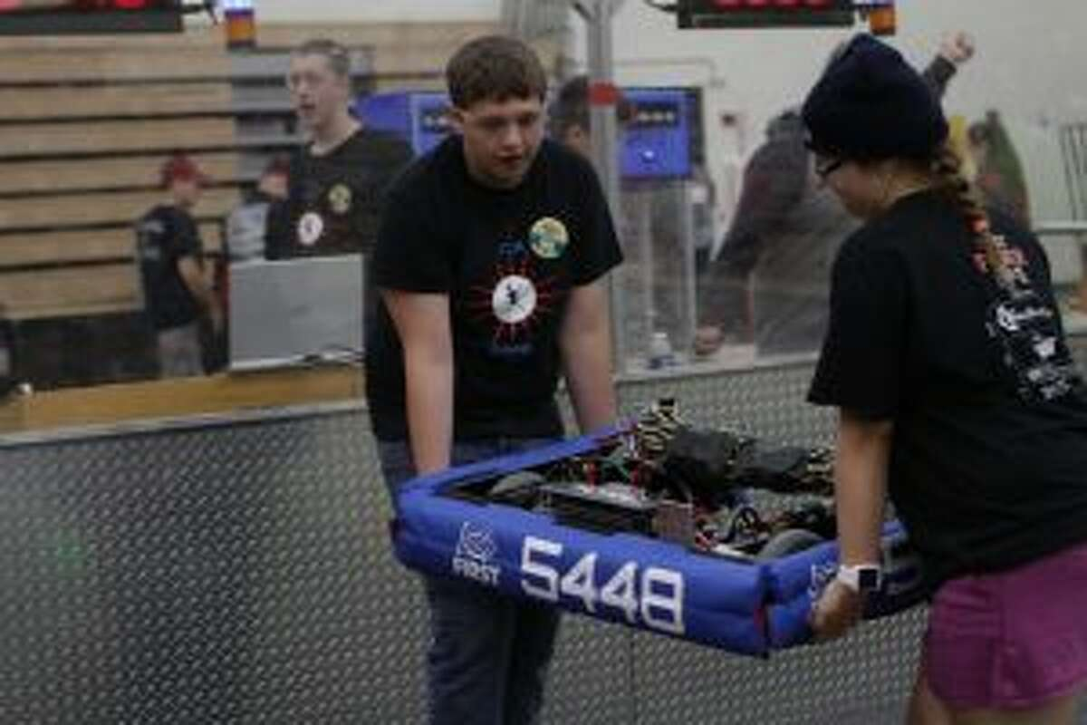 Crossroads Charter Academy students Kyle Bowen (left) and Kali Barstow carry their team's robot onto the field before the next match.