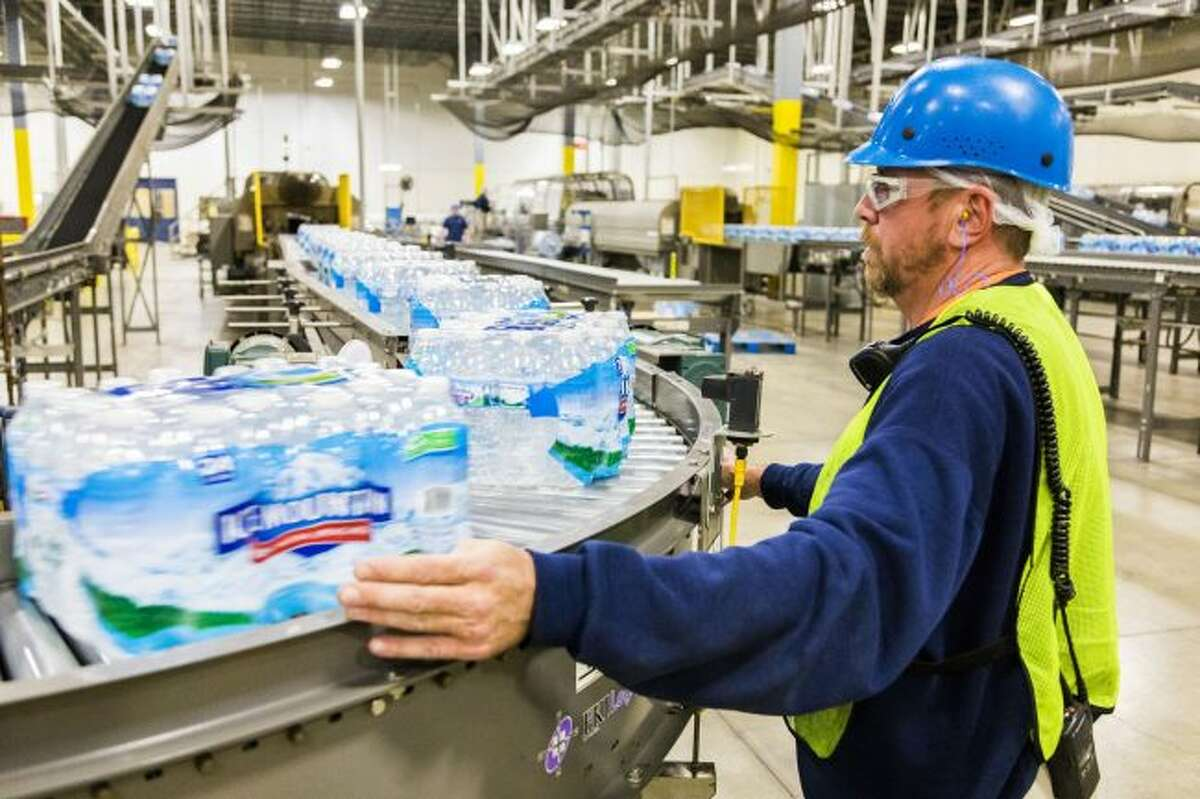 In this Pioneer file photo, Ice Mountain water is seen coming down the production line at Nestlé Waters North America's Ice Mountain bottling facility in Stanwood. The company received state approval in April to increase its water withdrawal capacity at its White Pine Springs well in Osceola Township, from 250 gallons per minute to 400 gallons per minute. (Pioneer file photo)