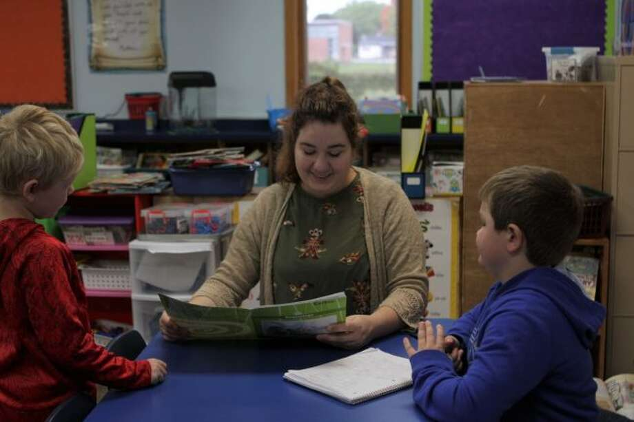 St. Peter's Lutheran School first- and second-grade teacher Grace Gilson (middle) works with Colton Richardson (left) and Eli Gielczyk (right) and their classroom assignments. Gilson is in her first full year of teaching at the school. (Pioneer photo/Meghan Gunther-Haas)