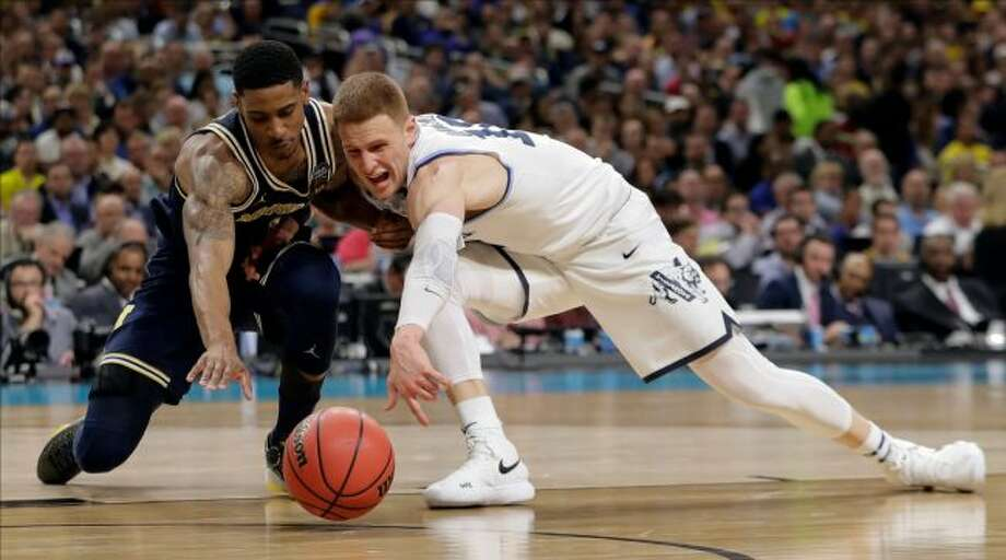 Michigan's Charles Matthews, left and Villanova's Donte DiVincenzo chase the loose ball during the second half in the championship game of the Final Four NCAA college basketball tournament, Monday, April 2, 2018, in San Antonio. (AP Photo/Eric Gay)