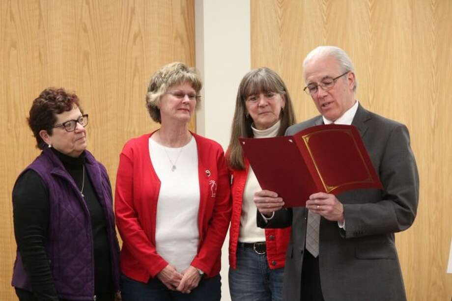 Surrounded by members of the General Federation of Women's Club Big Rapids, Mayor Tom Hogenson reads a special proclamation announcing Tuesday, April 24, as GFWC Federation Day during Monday's city commission meeting. Hogenson lauded the club for it enhancing the citizens and community of Big Rapids and the surrounding communities through members' commitment to volunteer services and financial support to organizations throughout the area. (Pioneer photo/Brandon Fountain)
