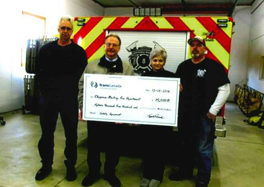 From left to right, Tim Nellis, TransCanada employee and Chippewa Township resident, and Larry London, TransCanada Community Investment representative, present the grant check to Julie Austin, Chippewa Martiny Fire Board treasurer and Brian David, Chippewa Martiny Fire chief. The grant money was used to purchase department and personnel equipment. (Courtesy photo)