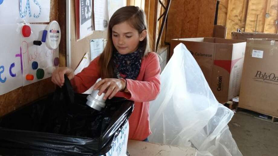 Ayla Ross, of Girl Scout Troop 4820, sorts through caps and lids in the collection box set up at Recycle of Mecosta County. Ross plans to collect 400 pounds of caps and lids to have a buddy bench built and placed in the area. (Pioneer photo/Meghan Gunther-Haas)