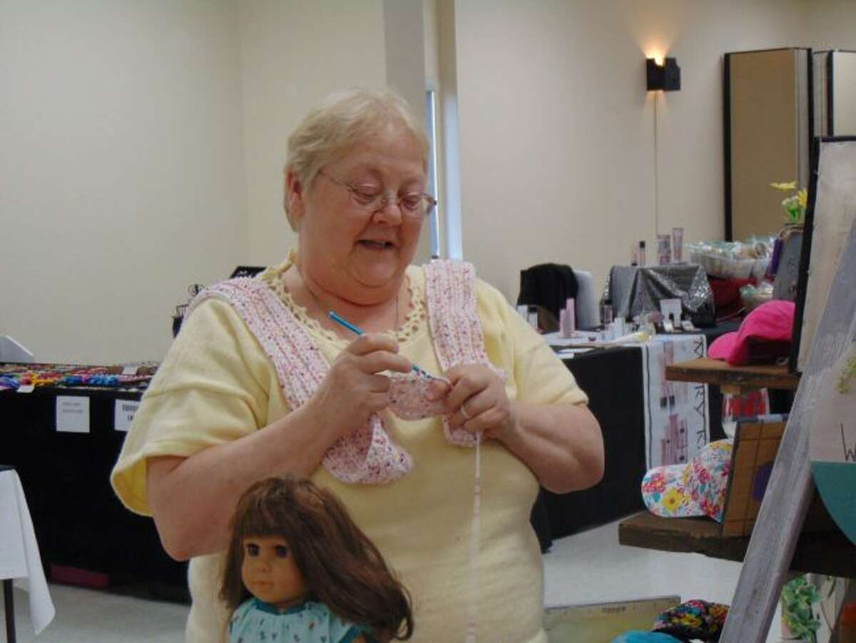 Crafter Kathy McKeever kept busy knitting while she waited on customers at her booth with blankets, children's clothing and other hand-knitted items for sale.