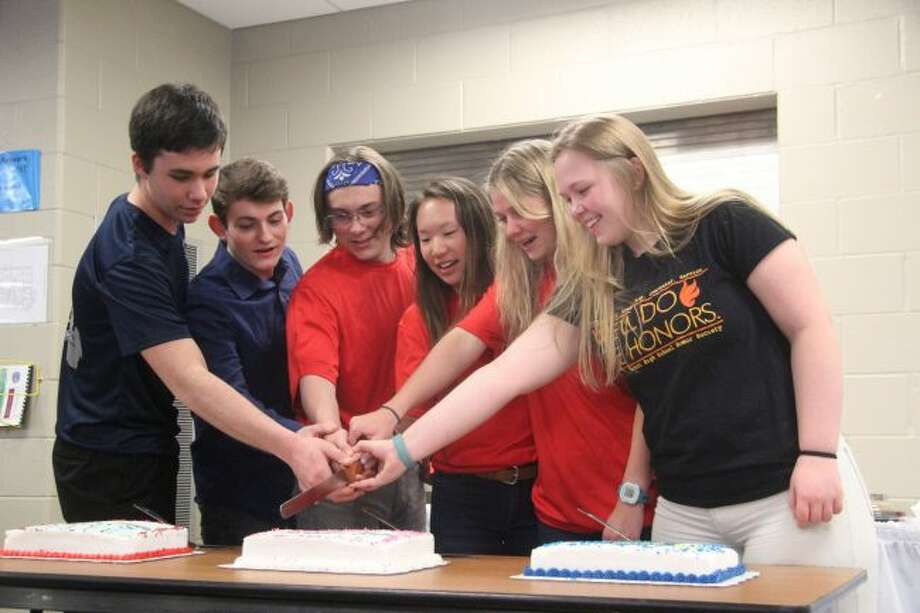 Students representing all of the schools in the Mecosta-Osceola Intermediate School District help to cut the ceremonial cake during Sunday's event at the Mecosta-Osceola Career Center to recognize the 33 students taking part in the American Legion Boys State and Ladies Auxiliary Girls State and Student Trooper programs. (Pioneer photo/Brandon Fountain)
