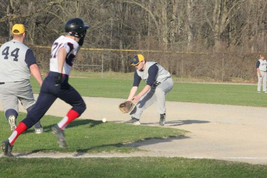 Crossroads' John Schultz (21) tries to beat the play at first base and would be called safe despite the efforts of Baldwin's Ian Lemieux (44) and Isaah Defrece (right). (Pioneer photo.John Raffel)