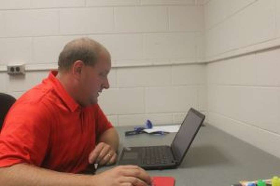 Chippewa Hills athletic director Mike Fosburg looks over his sports schedule.