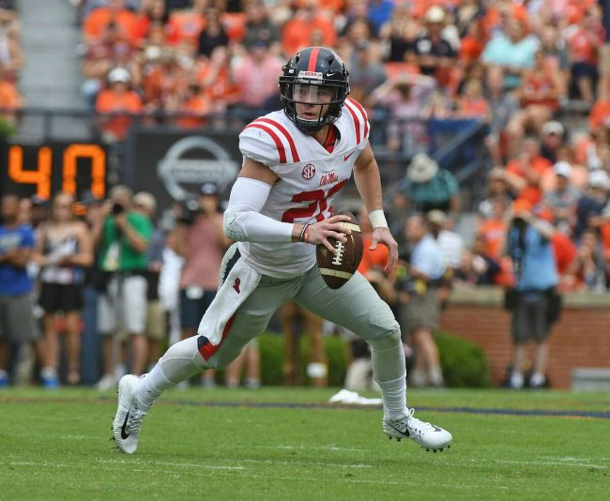 In this Oct. 7, 2017, file photo, Mississippi quarterback Shea Patterson (20) scrambles with the ball during the first half of an NCAA college football game against Auburn, in Auburn, Ala. Jim Harbaugh will lead Michigan through one more spring practice Tuesday, likely not knowing if Shea Patterson will be able to do more than practice in 2018. Two days later, most of the Wolverines are traveling to Paris to see some sights. By the time the Wolverines return from the trip, they hope to know if the NCAA will give Patterson a waiver to play instead of sitting out the season after transferring from Ole Miss. (AP Photo/Thomas Graning, File)