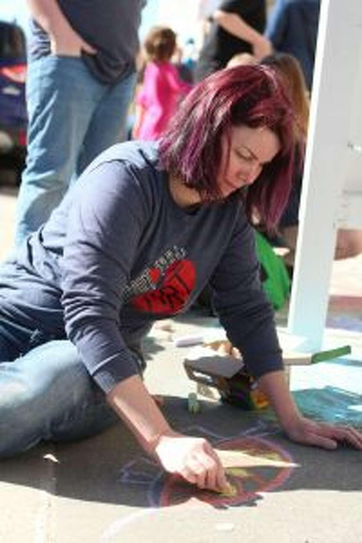 CELEBRATION: Nikki Jorgensen, owner of Heart-full ART Studio, works on a chalk drawing Saturday morning.