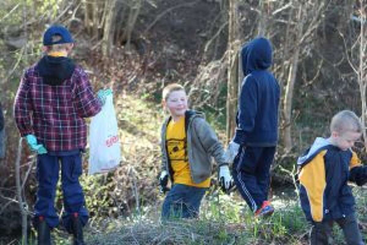 HELPING OUT: Members of Cub Scout Pack No. 3114 help clean up the banks of Mitchell Creek on Saturday morning in Big Rapids. Dozens and dozens of volunteers showed up to help pick up litter at the annual city-wide pick-up.