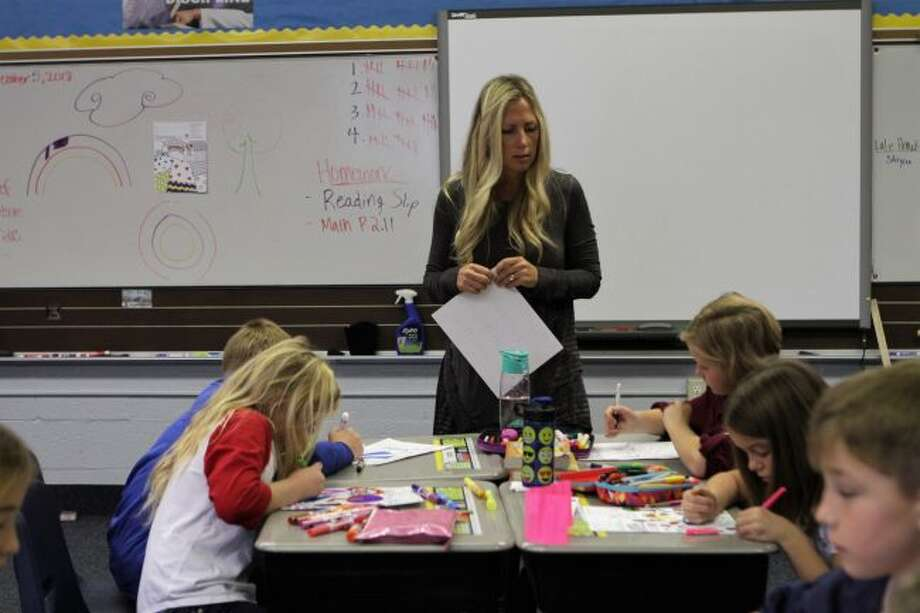 St. Mary Catholic School teacher Kristin Malloy talks with her fourth-grade students about an art project, in which they studied different patterns and media. This is Malloy's first year as a St. Mary teacher. (Pioneer photo/Meghan Gunther-Haas)