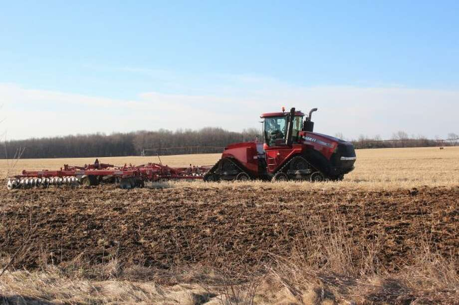A tracked tractor tills this Sackett Enterprise field on Seven Mile Road in Colfax Township on Wednesday morning. With warmer temperatures in the forecast, area farmers are preparing fields to plant crops. According to projected crop budgets from Jerry Lindquist, Michigan State University Extension grazing and crop management educator, wheat, alfalfa and soybeans are expected to be profitable this year for farmers. (Pioneer photo/Brandon Fountain)