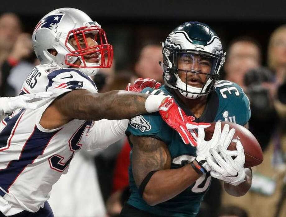 Philadelphia Eagles' Corey Clement, right, catches a touchdown pass in front of New England Patriots' Marquis Flowers during the second half of the NFL Super Bowl 52 football game in Minneapolis. While first-round picks receive most of the attention and players chosen the first two days of the draft get more money and better job security, success on Day 3 of the draft often separates the elite teams from the good ones. That was evident when the Eagles and Patriots met in February. Corey Clement had 100 yards receiving and one touchdown and LeGarrette Blount ran for 90 yards and one touchdown in Philadelphia's 41-33 victory. Danny Amendola led the Patriots with 152 yards receiving and Chris Hogan had 128. All four players were undrafted free agents. (AP Photo/Jeff Roberson, File)
