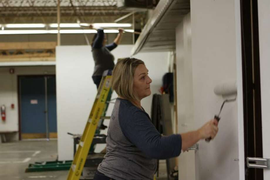 Mary Willmer (front), Gina Warmbein (back) and their peers, all of Independent Bank, spent Columbus Day off from work painting a retired room at Big Rapids Middle School. Th project was part of the bank's annual Making a Difference Day. (Pioneer photos/Meghan Gunther-Haas)