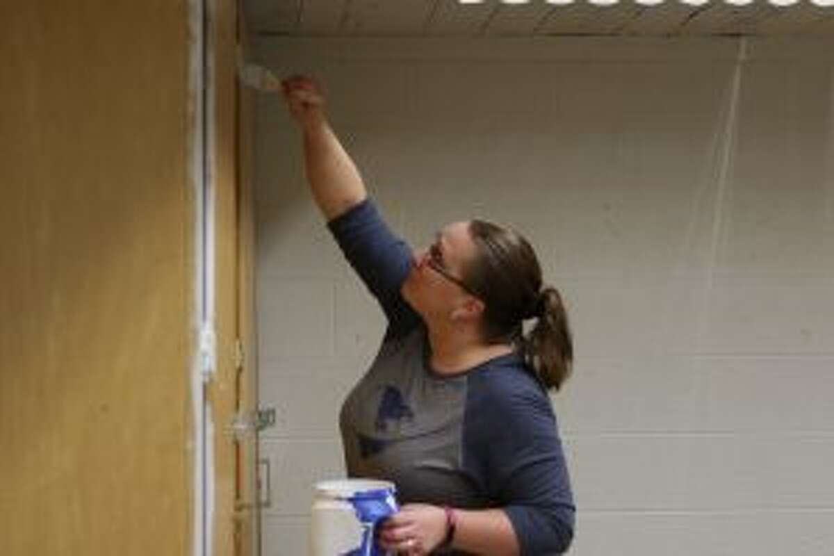 Deanna Coon begins painting cabinets which will be used in the project-based learning space once the room is finished.