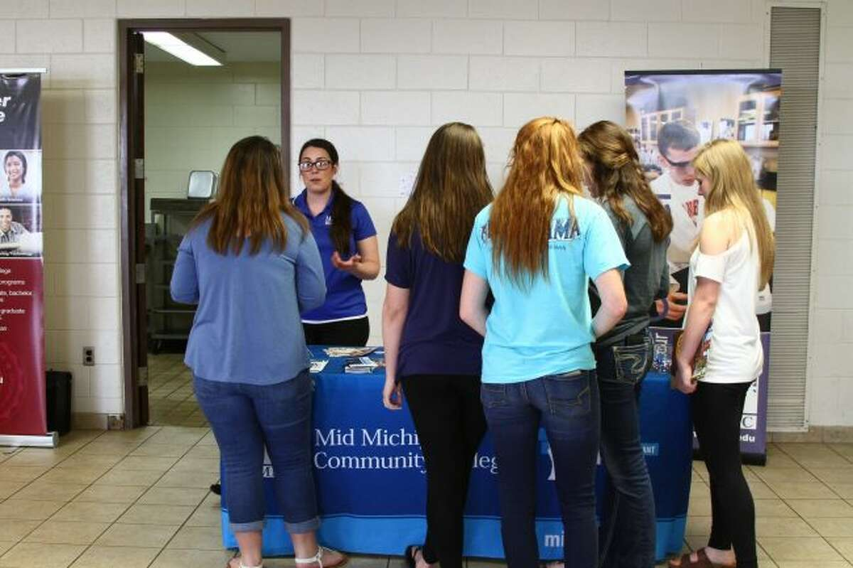 INFORMATION STATION: A group of Chippewa Hills High School students stop to visit the booth for Mid Michigan Community College during the college fair on Wednesday.