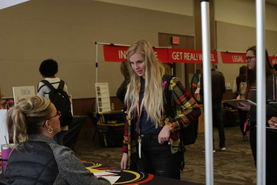 While traveling around one of the rooms in the University Center during Thursday's Get Real program, Ferris State University student Ashley Carpenter (standing) talks with FSU staff member April Bigelow about the costs of childcare. (Pioneer photos/Meghan Gunther-Haas)