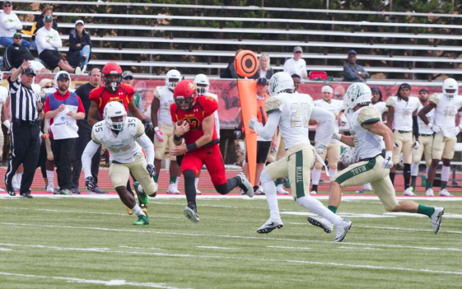 Ferris State quarterback Travis Russell tries to outrun Tiffin defenders after getting a first down during Saturday's game at Top Taggart Field. (Pioneer photo/Maxwell Harden)