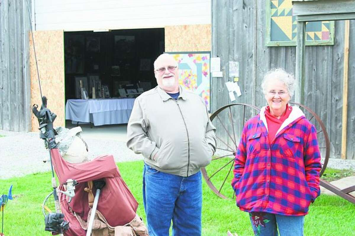 From left, Dan Lee and Karen Coville, who put on the art exhibit Two Artists in a Barn, pose outside of the barn, which is located one mile north of the M-66/M-20 intersection in Remus. The show will be open from 10 a.m. to 5 p.m. Saturday before closing for the season. (Pioneer photo/Tim Rath)