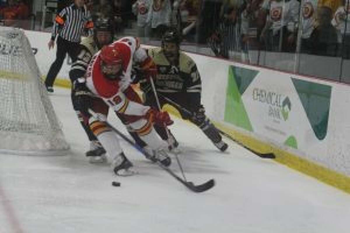 Zach Szajner (18) skates with the puck behind the net for Ferris.