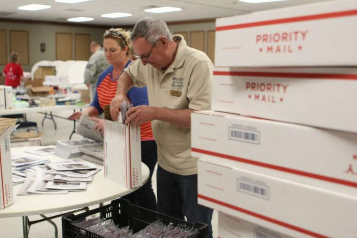 Fred Turk, of Decatur, helps stuff packages during the 15th Jerky for the Troops on Monday afternoon at CK's Place, south of Big Rapids. Along with 700 pounds of jerky snacks, personal items like toothpaste, baby wipes and books were packed in boxes to be shipped to service members around the world. (Pioneer photos/Brandon Fountain)