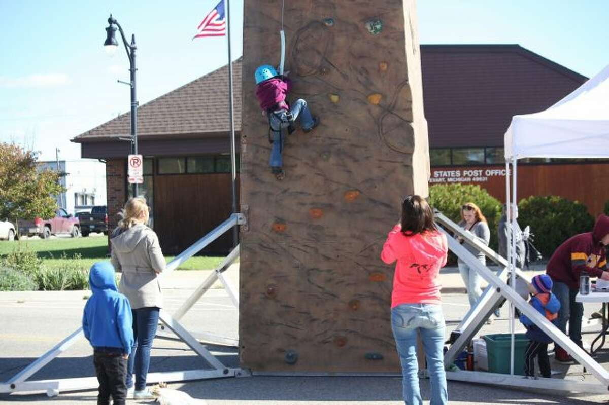 Four-year-old Ariana Romaro scaled halfway up the rock wall provided by Eagle Village as her family cheered her on.
