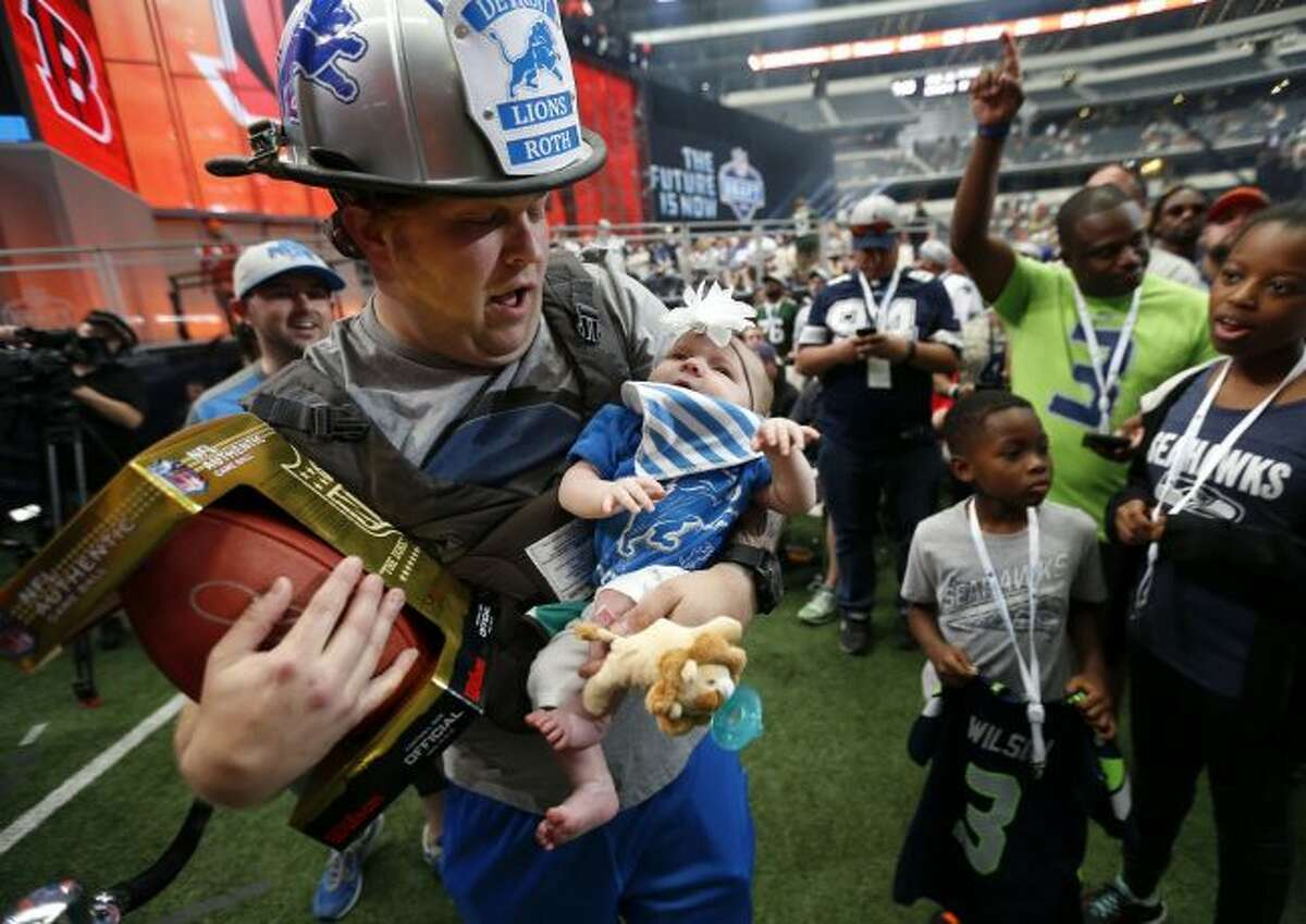 Detroit Lions fan Benjamin Roth, who is a firefighter at the Plano Fire Department, holds his 2-month-old daughter Isadora during the NFL football draft in Arlington, Texas, Saturday, April 28, 2018. (Jae S. Lee/The Dallas Morning News via AP)
